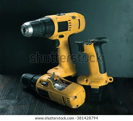 Electric drills on the wooden table - stock photo