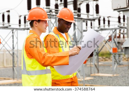 electric engineers discussing blueprint in substation - stock photo