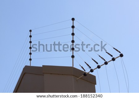 electric fence against blue sky atop boundary wall - stock photo