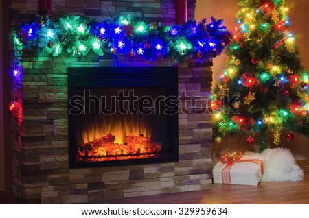 Electric fireplace and Christmas tree, decorated with garlands with colored lights - stock photo