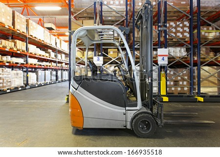 Electric forklift in distribution warehouse - stock photo