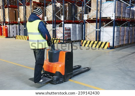 Electric forklift pallet stacker truck equipment at work in warehouse - stock photo