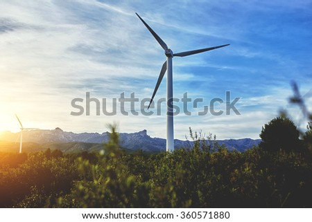 Electric generators located in countryside with beautiful landscape on background, wind turbines against cloudy sky and  sun rays, alternative energy resources  - stock photo