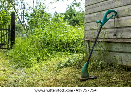 electric grass trimmer stands in the garden near the house, simply supported on the wall - stock photo