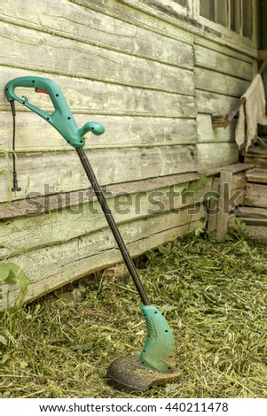 electric grass trimmer stands in the garden near the house, simply supported on the wall