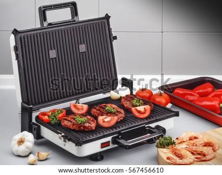Electric Grill With Burgers And Prawns On Kitchen Board