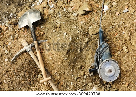 electric grinder, pick and shovel for mason construction workers  to repair  tiles in  the sidewalk in street city  - stock photo