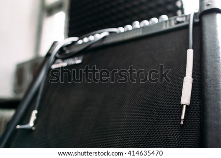 Electric guitar amplifier with silver knobs and cable closep. Selective focus technique on  professional guitar amplifier knobs - stock photo