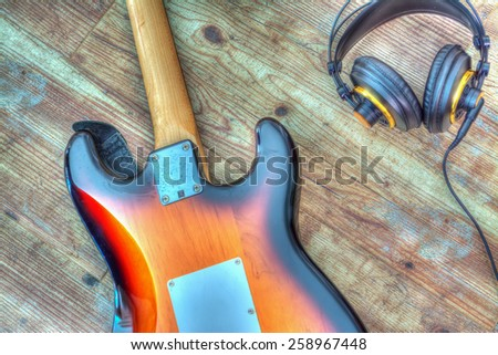 electric guitar and headphones on a wooden board. Processed for hdr tone mapping effect - stock photo
