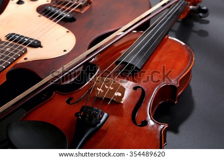 Electric guitar and violin on grey background - stock photo