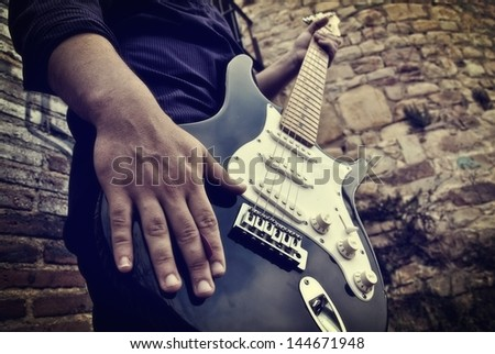 electric guitar being played by a rocker - stock photo