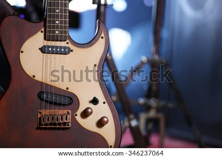 Electric guitar close-up, on dark background - stock photo