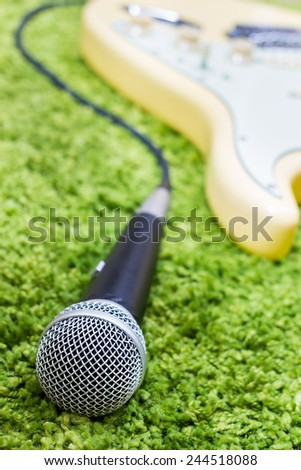 electric guitar & dynamic microphone on green / green music concept - stock photo