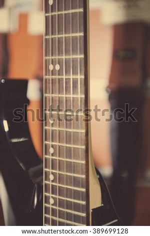 Electric guitar fingerboard against colorful background