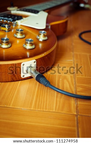 Electric guitar honey burst color on floor with jack cable - stock photo