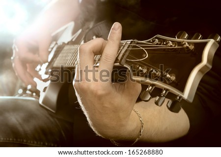 Electric guitar in male hands - stock photo