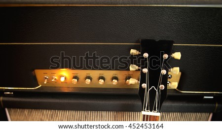 Electric Guitar leaning against an amplifier with control panel and knobs and toggle switches - power light glowing - stock photo