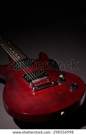 Electric guitar mahogany, dark background, vertical composition, a stringed musical instrument, electronic control bodies, six-string guitar, tuning and adjustment. - stock photo