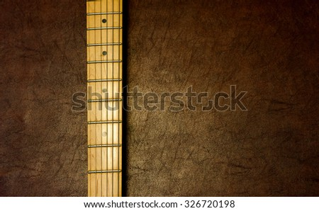 Electric guitar neck vertical detail on wooden background vintage look