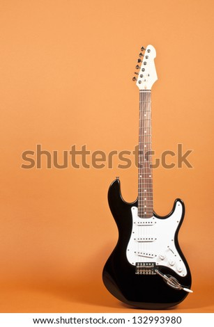 Electric guitar on orange backdrop - stock photo