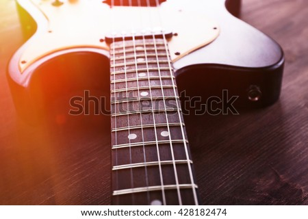 Electric guitar on wooden background with light effect - stock photo