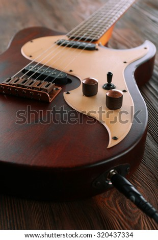 Electric guitar on wooden table close up - stock photo
