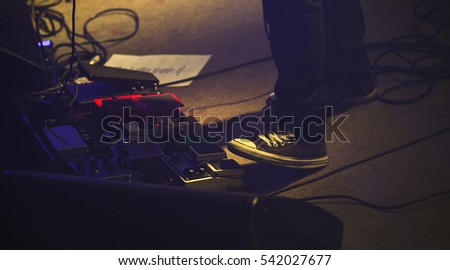 Electric Guitar Player On A Stage With Set Of Distortion Effect Pedals Under His Foot
