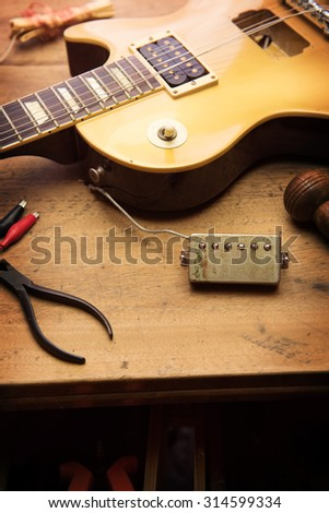 Electric guitar repair. Vintage electric guitar on a guitar repair shop work bench. gold color. shallow depth of view, intentionally shot with low key shadows. - stock photo