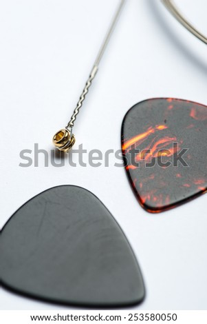Electric guitar string with two mediators on white surface - stock photo