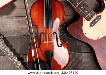 Electric guitar, violin, soprano saxophone and book on wooden background - stock photo
