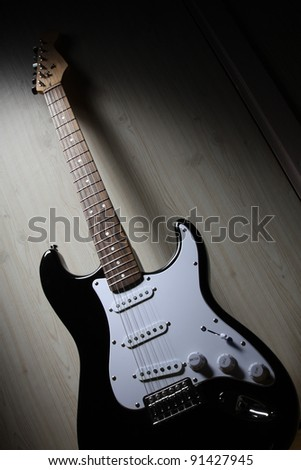 Electric guitar waiting in shade - stock photo