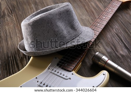 Electric guitar with hat on wooden background - stock photo