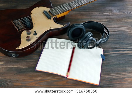 Electric guitar with headphones and notebook on wooden table close up - stock photo