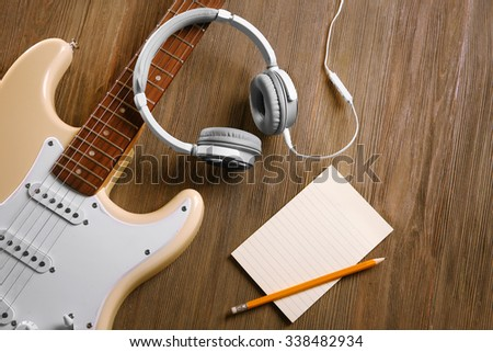 Electric guitar with headphones on wooden background - stock photo