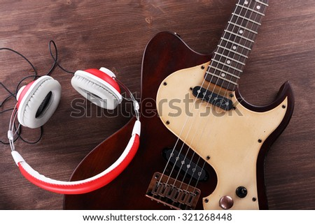 Electric guitar with headphones on wooden table close up - stock photo