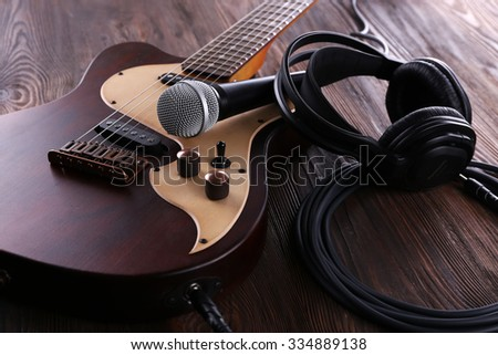 Electric guitar with microphone and headphones on wooden table close up - stock photo