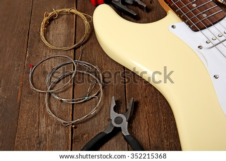 Electric guitar with pliers and cords on wooden background, close up - stock photo