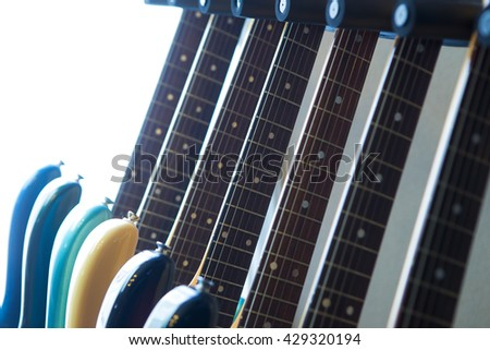 Electric guitars on a guitar rack by a sunlit window. Shallow depth of field. - stock photo