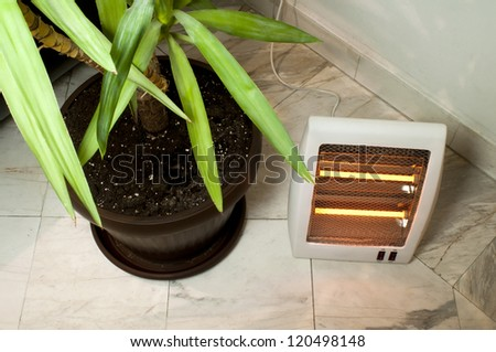 Electric heater with halogen coils. Flower pot and heater on marble slabs - stock photo