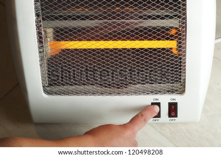 Electric heater with halogen coils. Hand which includes switch - stock photo
