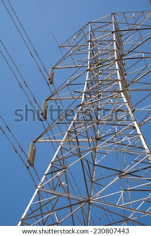 electric high voltage power post with blue sky background