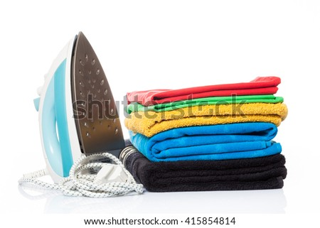 Electric iron and pile of clothes. electric iron isolated on white
