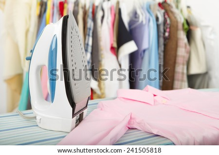 Electric iron and shirt, on cloth background  - stock photo