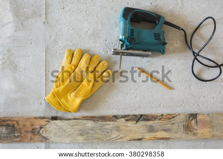 Electric jig saw and yellow gloves - stock photo