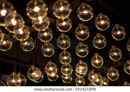 electric lamps hanging on the ceiling in the dark room - stock photo
