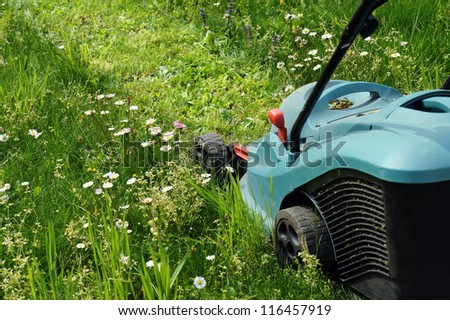 electric lawn mowers running on green