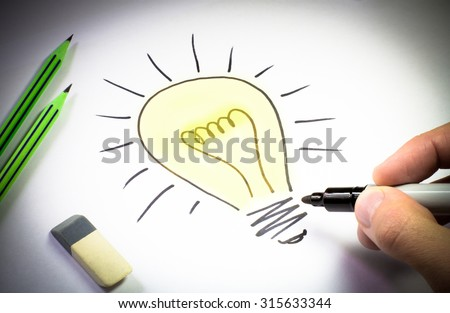 electric light bulb drawing on a white sheet of paper - stock photo