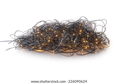 Electric lights need to be unraveled before decorating the christmas tree, isolated on white background - stock photo