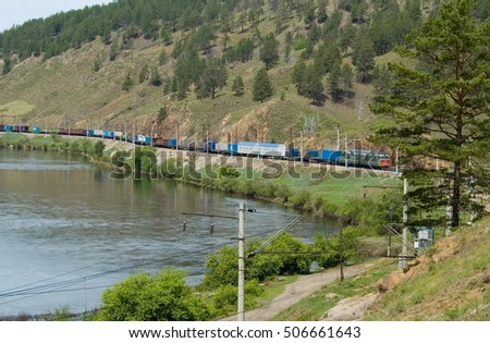 electric locomotive driven freight train at Lake Baikal (Siberia, Russia) along the river with views of the mountains
