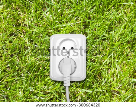 Electric outlet on green grass  - stock photo